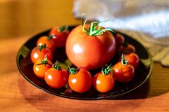 Czerwoni pomidory w czarnym talerzu na kuchennym stole obok Notepad zdjęcia stock