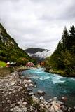 Czerwoni scandinavian drewniani domy i kabiny przy i turkusową rzeką otaczającymi dzikimi, szybkimi i górami i gęstymi pierwszymi Fotografia Stock