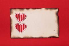 Czerwoni serca i burnt papier Zdjęcia Stock