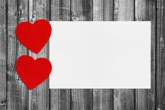 Czerwoni serca i pusty papier na czarny i biały drewnie obrazy stock