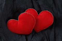 Czerwoni serca na czerń papieru tle Obraz Stock