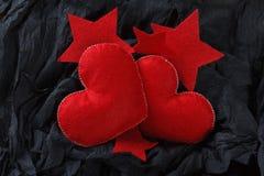 Czerwoni serca na czerń papieru tle Fotografia Stock