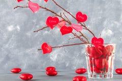 Czerwoni serca z wpisowym miłości zrozumieniem na gałąź na szarości betonują tło odosobnionego loga miłości przedmiota znaka drze Zdjęcie Royalty Free