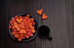 Czerwoni sercowaci ciastka na czarnym talerzu, kawowy kubek, walentynka dzień Obrazy Royalty Free