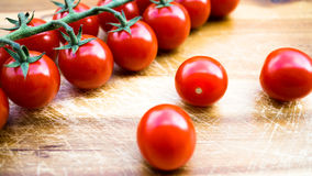 Czerwoni soczyści pomidory na tnącej desce Zdjęcie Stock