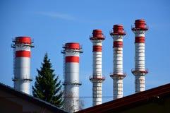 Czerwoni szczegółu przemysłu kominy i zielony drzewo zdjęcia royalty free