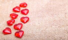 Czerwoni szklani serca kłamają na pielusze od grabić Obrazy Royalty Free