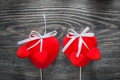 Czerwoni tkanin serca z białymi faborkami na drewnianej deski świętowaniu Zdjęcie Stock