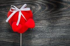 Czerwoni tkanin serca z białymi faborkami na drewnianej deski wakacjach co Obrazy Royalty Free