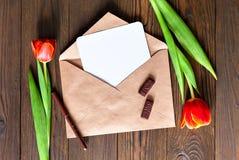 Czerwoni tulipany i Kraft koperta na drewnianym tle Obraz Stock