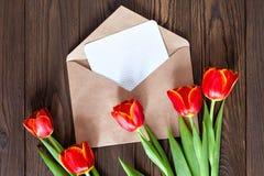 Czerwoni tulipany i Kraft koperta na drewnianym tle Obraz Royalty Free
