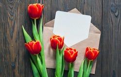 Czerwoni tulipany i Kraft koperta na drewnianym tle Fotografia Royalty Free