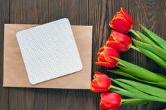 Czerwoni tulipany i Kraft koperta na drewnianym tle Zdjęcia Royalty Free