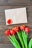 Czerwoni tulipany i Kraft koperta na drewnianym tle Obrazy Stock
