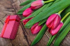 Czerwoni tulipany i prezent na drewnianym stole Fotografia Royalty Free