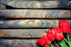 Czerwoni tulipany na ciemnych deskach Zdjęcia Stock