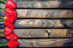 Czerwoni tulipany na ciemnych deskach Zdjęcie Royalty Free
