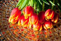 Czerwoni tulipany na mozaika stole. Obrazy Stock
