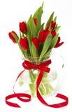 Czerwoni tulipany w wazie z czerwonym faborkiem Zdjęcia Stock