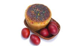 Czerwoni Wielkanocni jajka i Wielkanocny chleb w koszu na białym backgrou Obraz Stock