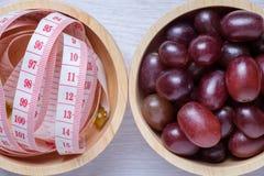 Czerwoni winogrona i taśmy miara w drewnianym pucharze Obraz Royalty Free