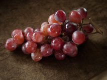 Czerwoni winogrona na Brown płótnie zdjęcie royalty free