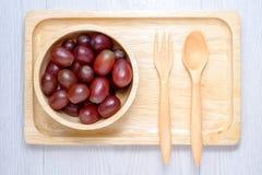 Czerwoni winogrona w drewnianym pucharze i łyżce Zdjęcie Stock