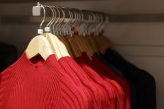Czerwoni woolen trykotowi pulowery wiesza na wieszakach w sklepie, w górę zdjęcia stock