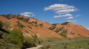 Czerwoni wzgórza z drogą gruntową i bufiastymi białymi chmurami Obrazy Stock