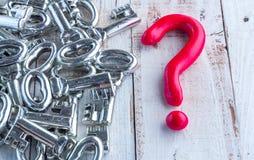 Czerwoni znaka zapytania i srebra klucze na drewnianym stole jpg Zdjęcia Stock