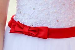Czerwony łęk na ślubnej sukni Fotografia Stock