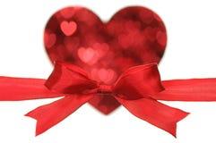Czerwony łęk na kierowym kształcie małym sercem. Obrazy Stock
