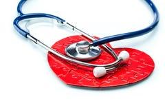 Czerwony łamigłówki serce z stetoskopem odizolowywającym na białym tle Obrazy Royalty Free