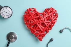 Czerwony łozinowy serce na błękitnym stole obok ciśnienie krwi mankiecika, stetoskopu i fotografia stock
