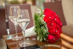 Czerwony ślubny bukiet kwiaty Ślubny bukiet czerwone róże i dwa szampańskiego szkła stoi na autentycznym Tło wi Fotografia Stock