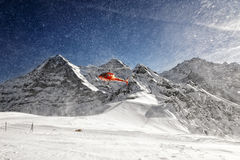 Czerwony śmigłowcowy brać z śniegu proszkiem chmurnieje od wysokogórski ponownego Zdjęcia Stock