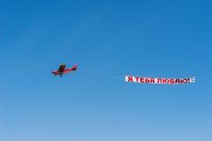 Czerwony śmigłowy samolot w niebieskim niebie z sztandarem kocham ciebie obraz stock