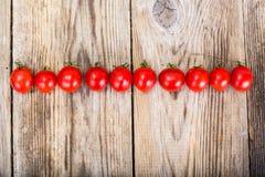 Czerwony Świeży Czereśniowy pomidor na Drewnianym Nieociosanym tle Zdjęcia Royalty Free