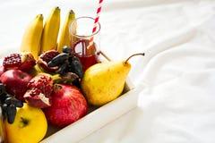 Czerwony świeży sok z jabłkami, bonkretami, bananami, winogronami i granatowiec owoc w białej drewnianej tacy na łóżkowym prześci Fotografia Royalty Free