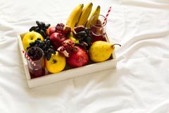 Czerwony świeży sok z jabłkami, bonkretami, bananami, winogronami i granatowiec owoc w białej drewnianej tacy na łóżkowym prześci Zdjęcia Royalty Free