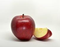 Czerwony żółty jabłko z zielonym liściem i plasterkiem Obraz Stock