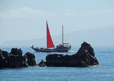 Czerwony żagla czerń kołysa ocean fotografia stock