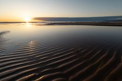 Czerwony żywy zmierzch przy morzem bałtyckim z lustrem jak woda Veczemju Klintis Latvia, Kwiecień, - 13 - Żebrować fale i pi obraz royalty free
