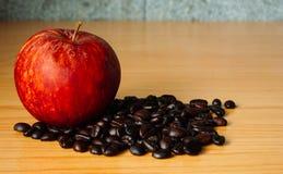 Czerwony Apple i Kawowa fasola na drewnianym stole Zdjęcia Royalty Free