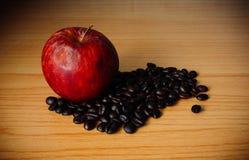 Czerwony Apple i Kawowa fasola na drewnianym stole Zdjęcie Royalty Free