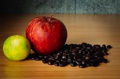 Czerwony Apple, wapno i Kawowa fasola na drewnie, Obraz Royalty Free