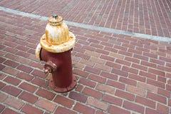 Czerwony biały rdzewiejący pożarniczy hydrant na ceglanym przejście chodniczku obraz stock