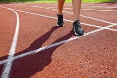 Czerwony bieg ślad z żeńskim biegaczem, zamyka up na nogach Obrazy Royalty Free