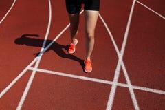 Czerwony bieg ślad z żeńskim biegaczem, zamyka up na nogach Zdjęcie Royalty Free