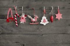 Czerwony biel sprawdzał boże narodzenie dekoraci obwieszenie na stary drewnianym Fotografia Stock